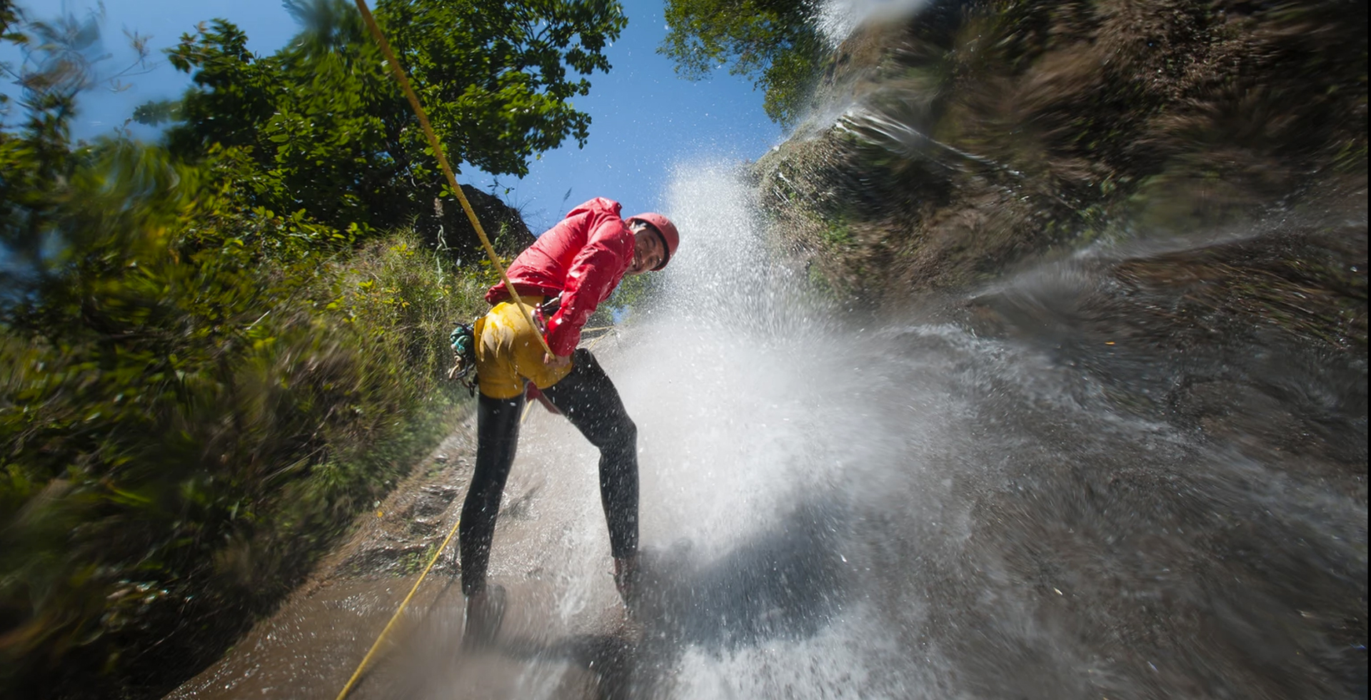 Man repelling down with a rope from a waterfall